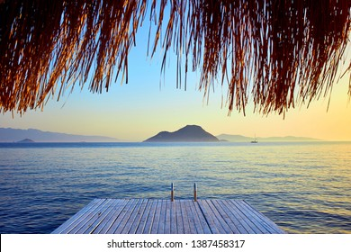 Bungalow on the sea at sunset. Wooden pavilions on the shore of a sandy beach - Bodrum, Turkey