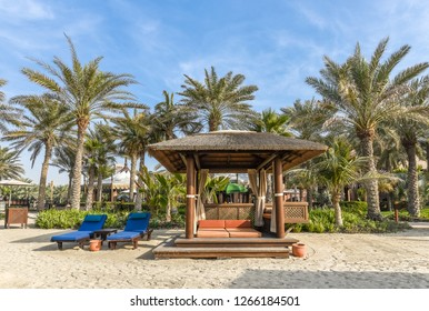 Bungalow with sun beds on a beautiful sandy beach with palm trees.