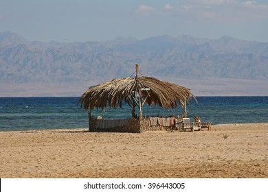 Bungalow and two wooden chairs on the shore of the Suez Canal in Egypt.