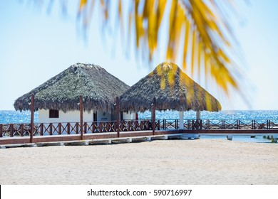 bungalows on tropical beach on blue sky background