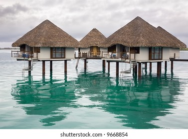 Bungalows standing over colorful lagoon waters at evening.