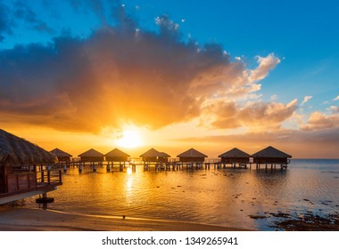 Bungalows at sunset in the lagoon Huahine, French Polynesia. Copy space for text