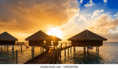 Bungalows at sunset in the lagoon Huahine, French Polynesia