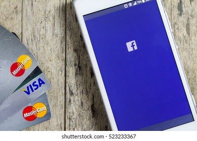 BUNGKAN, THAILAND - NOVEMBER 10, 2015: smart phone with Facebook on screen and credit cards on wood background