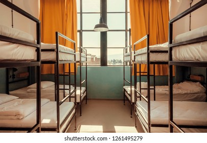 Bunk beds inside bedroom with big window and yellow curtains.