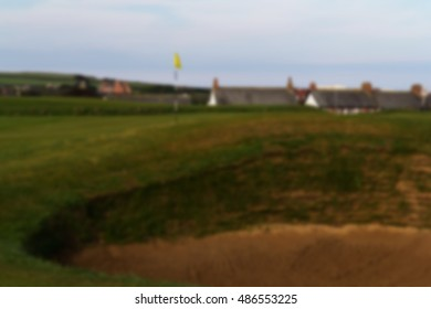Bunker on golf course with green behind Out of focus.