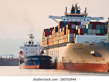 Bunkering tanker Vitaly Vanyhin a large container ship Cosco company. Nakhodka Bay. East (Japan) Sea. 01.08.2014
