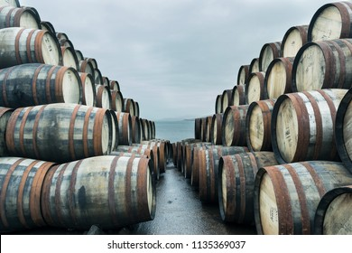 Bunnahabhain distillery, Islay, Scotland. Lots of weathered whisky casks are stacked up outside Bunnahabhain distillery Islay. Feb 2017
