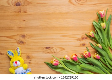 Bunny and a bouquet of flowers on a wooden table, blank
