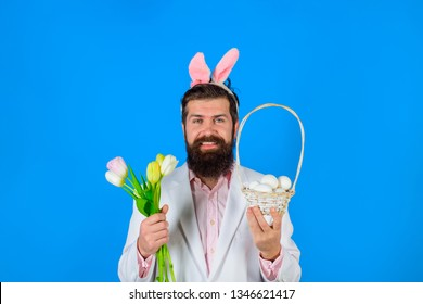 Bunny ears. Preparing for Easter. Happy Easter. Bearded man. Flowers bouquet. Spring holiday. Spring flowers. Easter eggs. Eggs hunt. Rabbit costume. Rabbit mask. Religion symbol. Tradition of Easter.