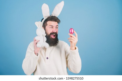 Bunny and egg. Celebration of spring time holiday. Bearded man with bunny toy and Easter egg. Hipster with long rabbit ears holding egg laying hare. Easter bunny delivering colored eggs, copy space.