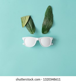 Bunny rabbit face made of natural green leaves with sunglasses on pastel blue background. Happy Easter minimal concept. Flat lay.