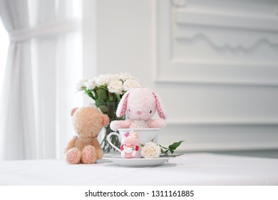 bunny and teddy. Cute stuffed animals of pink rabbit doll and brown teddy bear sitting together. Love and friendship concept. Soft focus on the bunny doll.