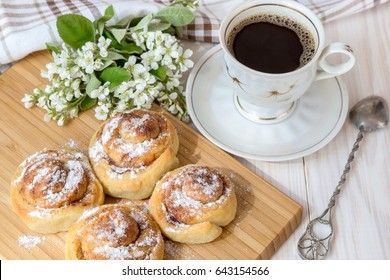 Buns with cinnamon and a cup of coffee on a light wooden table.