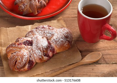 Buns with jam and cup of tea on old wooden table