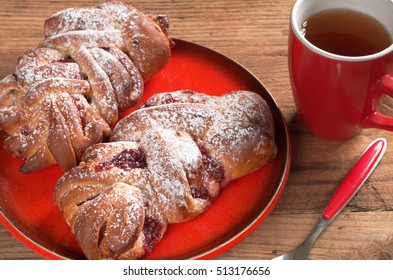 Buns with jam in red plate and cup of tea on old wooden background