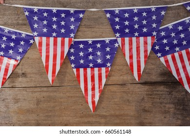 Bunting flags arranged on wooden table with 4th July theme
