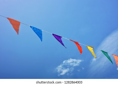 Buntings of different colors against blue sky put up for a festive festival celebration