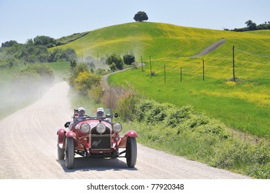 BUONCONVENTO (SIENA), ITALY - MAY 14: A 1934 built red Fiat Balilla 508S Coppa D'oro driven by O. Peli and S. Reboldi during a time trial at 1000 Miglia race on May 14, 2011 near Buonconvento (Siena), Italy