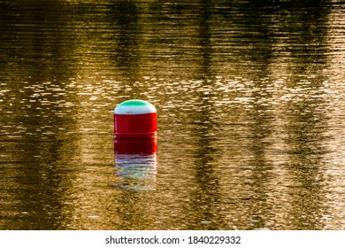 Buoy on the lake, reflections of trees in water in background