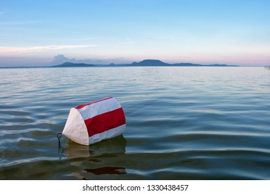 Buoy with red and white stripes on the blue water of Lake Balaton with the Badacsony mountan in the background after sunset in Hungary