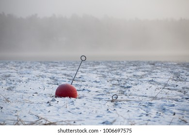 Buoy stuck in the ice on a misty lake.
