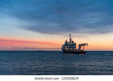 Buoy-Laying Vessel departing from Dun Laoghaire harbor at sunrise in Dublin, Ireland. Seascape with an advanced multifunctional ship in the Irish Sea at dusk.