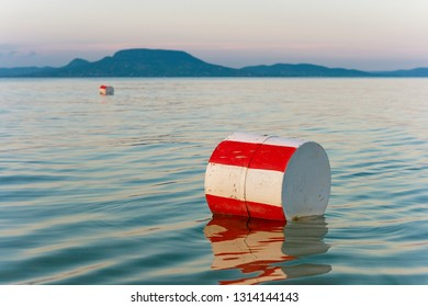 Buoys with red and white stripes on the blue water of Lake Balaton with the Badacsony mountan in the background in Hungary