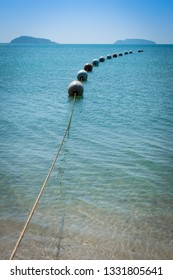 Buoys strung together on beautiful blue sparkling waters and clear sea. Safety buoys to create safe swimming area .