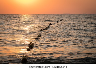 Buoys strung together on beautiful sea wave in sunset time. Safety buoys to create safe area in evening time .