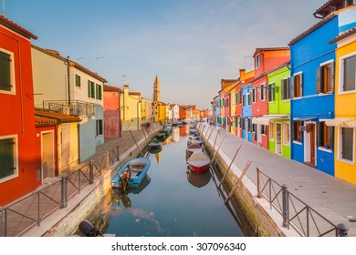 BURANO, ITALY - 14TH MARCH 2015: A view of streets of Burano at sunset showing the colourful buildings, boats and a tower