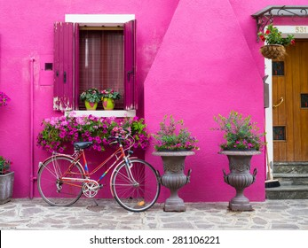 Burano, Italy - 21 May 2015: Painted building with bicycle in front. One of the many different coloured painted buildings on the island of Burano near Venice,