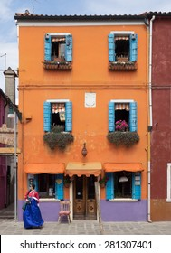 Burano, Italy - 21 May 2015: Brightly painted building. One of the many different coloured painted buildings on the island of Burano near Venice, Italy. Japanese tourist in Kimono walking past