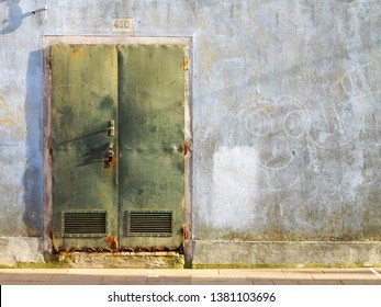 Burano, Italy - 24 February 2019 - A green door in a blue wall on the island of Burano, Italy. Burano is near Venice, and is famous for its canals and charming colourful houses.