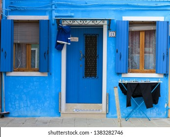 Burano, Italy - 24 February 2019 - The facade of a blue house with a laundry rack outside in Burano, Italy.  Burano is near Venice, and is famous for its canals and charming. colourful houses.