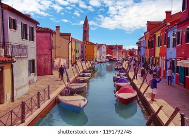 BURANO, ITALY - APR 16, 2018 - Brightly painted houses and small boats in canal on the island of Burano Venice, Italy