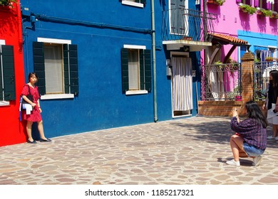BURANO, ITALY - AUG 11, 2018 - Tourists pose for pictures in front of  brightly painted houses on the island of Venice, Italy