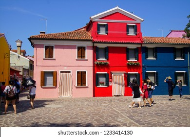 BURANO, ITALY - AUG 11, 2018 - Brightly painted houses line a square on the island of Burano, Venice, Italy