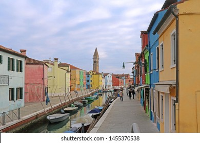 Burano, Italy - January 10, 2017; Tourists walking along famous Burano streets in Italy during winter. Street canal on Burano island with docked boats and colorful facade houses.
