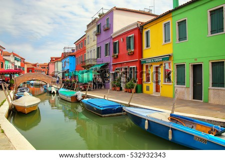 BURANO, ITALY - JUNE 22: Colorful houses by canal on June 22, 2015 in Burano, Italy. Burano is an island in the Venetian Lagoon and is known for its lace work and brightly colored homes.