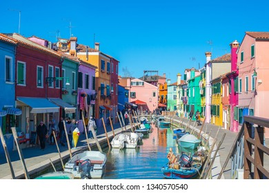 Burano, Italy. March 2019: Colorful houses facades on the bank of a canal.