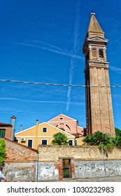 BURANO, ITALY - MAY 21, 2017: View of the back of the Leaning Bell Tower from the street in Burano, Italy.