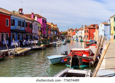Burano, Italy - October 7, 2017: Tourists and colourful houses along the canal on the Venetian island of Burano, Venice lagoon