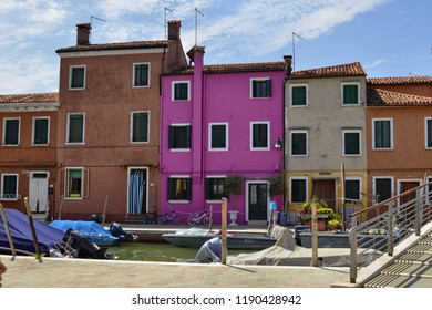 Burano, Venetian Lagoon, Veneto region, Italy. August 2018. The fantastic colorful houses of Burano. They have bright colors, the facades are mirrored in the canals. Tourists enjoy the show.