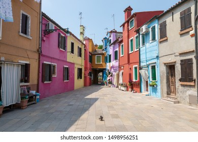 Burano, Venice, Italy - July 2, 2018: Panoramic view of brightly coloured homes of Burano is an island in the Venetian Lagoon. People walk and rest on streets. Summer sunny day and blue sky