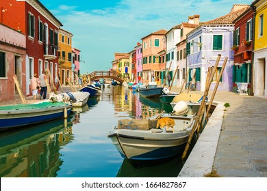 BURANO, VENICE, ITALY - OCTOBER 15, 2018: Street with colorful buildings and canal in Burano island, Venice, Italy