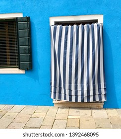 Burano, Venice/Italy-04/26/2015:Blue House with Blue and White Striped Curtain and Window in Burano, Venice, Italy.