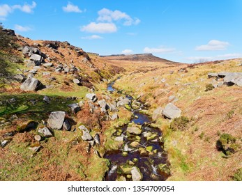 Burbage Brook winds across the Derbyshire Peak District with Higger Tor in the backgound