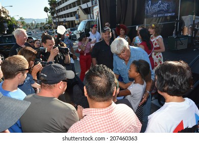 BURBANK, CA - JULY 26, 2014: Former Tonight Show host Jay Leno greets a young fan at the Downtown Burbank Car Classic.