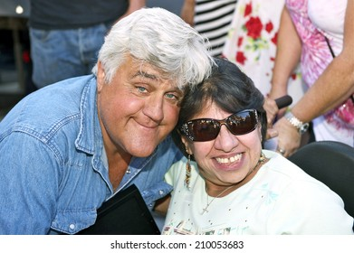 BURBANK/CALIFORNIA - JULY 26, 2014: Jay Leno former host of the Tonight Show poses for a picture with a fan at the Burbank Car Classic July 26, 2014, Burbank, California USA
